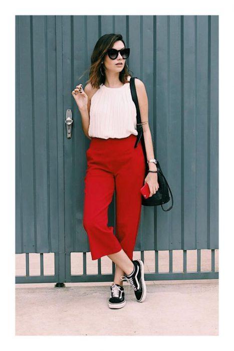 pantalon rojo con remera negra y zapatillas