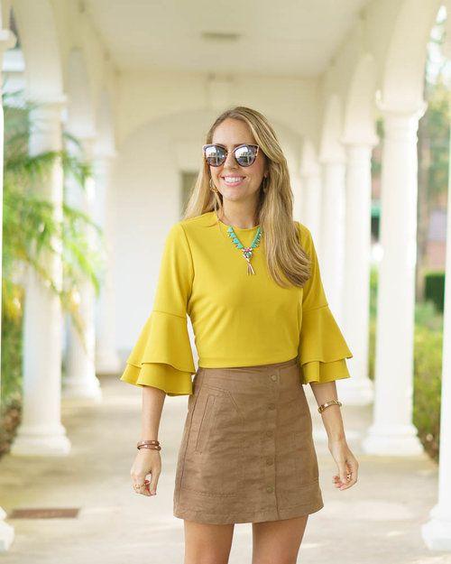 blusa amarilla con falda camel