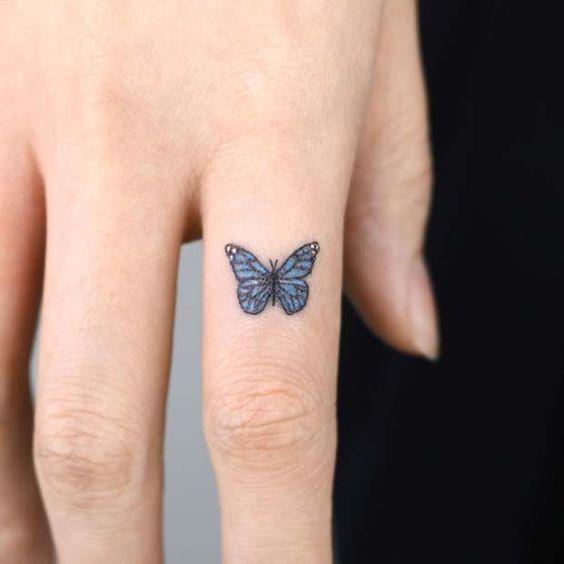 Tatuaje del dedo para mujer mariposa azul