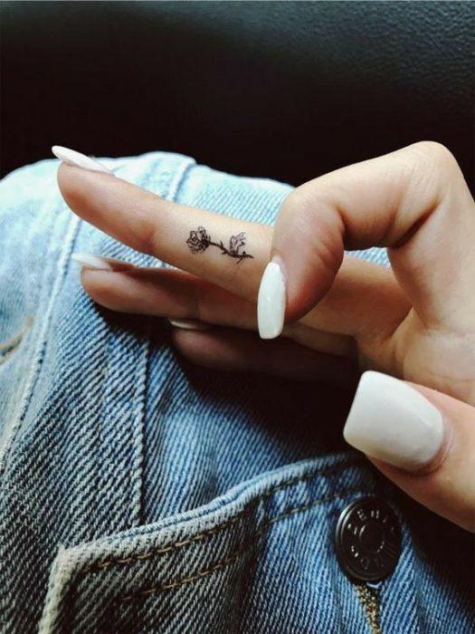 Tatuaje del dedo para mujer rosa con espinas