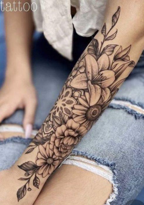 Tatuaje en parte exterior antebrazo flores