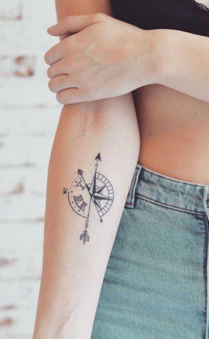 Tatuaje en parte interior antebrazo brujula y reloj