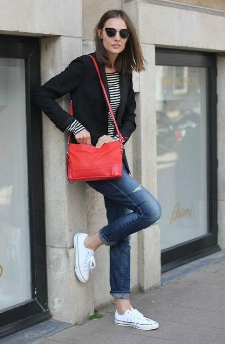 cartera roja y zapatillas blancas