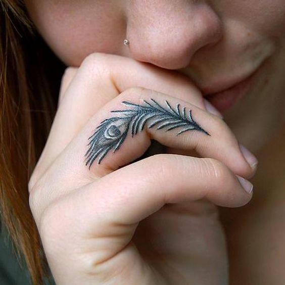 tatuaje de pluma de pavo en el dedo