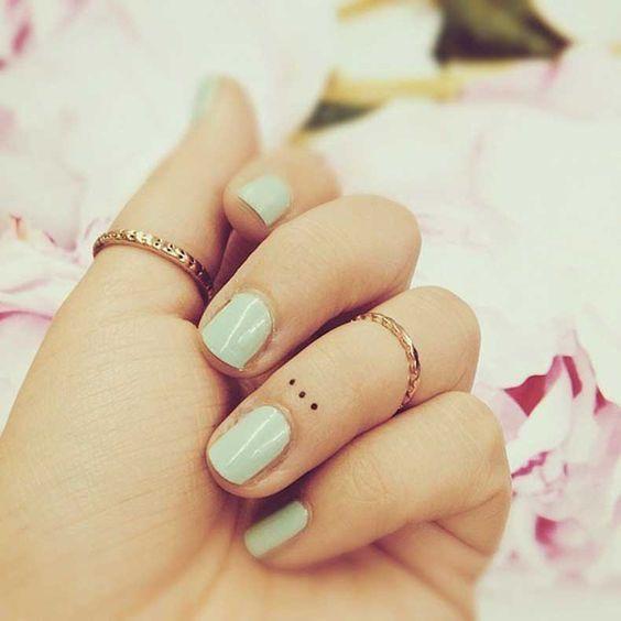 tatuaje de puntos suspensivos en dedo